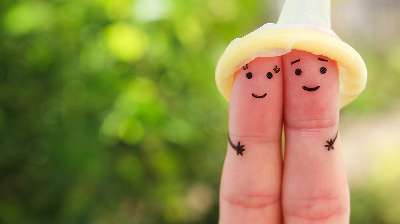 Zwei mit Gesichtern bemalte Finger tragen ein Kondom als Hut als Symbol für den Schutz vor Geschlechtskrankheiten.