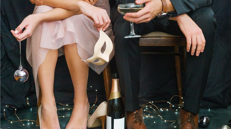 Die Leber schonen: Eine Frau und ein Mann sitzen nebeneinander, umringt von Christbaumschmuck, Sektflasche und Gläsern.