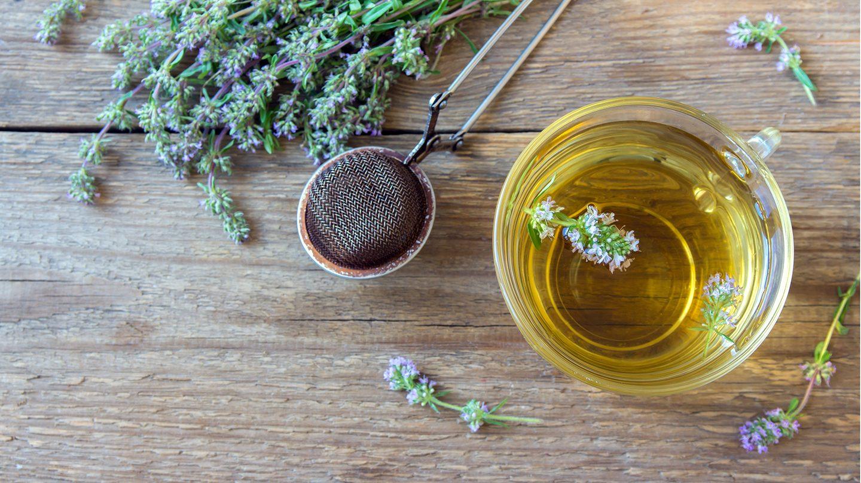 Husten stillen: Ein Glas mit Kräutertee, ein Teesieb und getrockneter Thymian sind auf einem Holztisch angeordnet.
