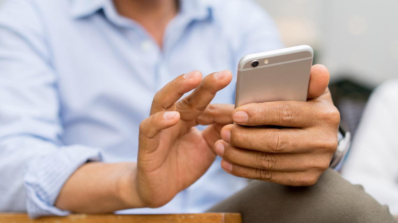Corona-Warn-App: Mann in blauem Hemd tippt mit Fingern auf einem Smartphone.