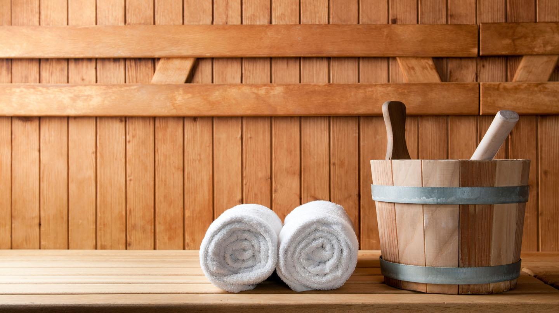 Abwehrkräfte stärken: Vor der Holzwand einer Sauna liegen zwei weiße zusammengerollte Handtücher, daneben steht ein kleiner Holzeimer.